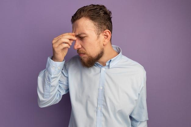 失望したハンサムなブロンドの男は、鼻に手を置き、紫の側を見て