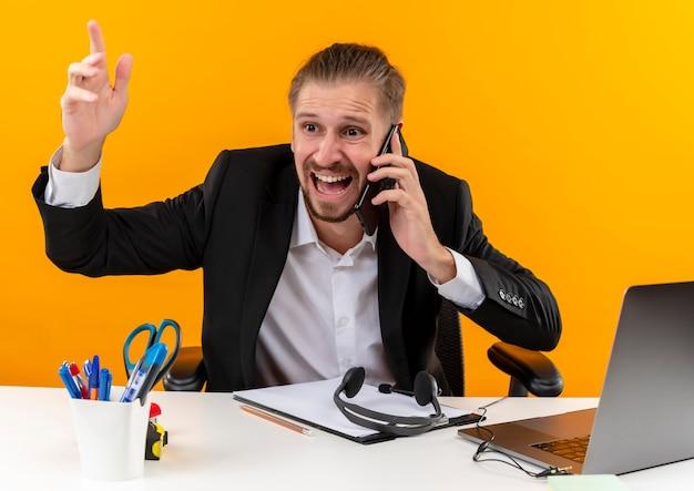 오렌지 배경 위에 사무실에서 테이블에 앉아 혼란스럽고 불쾌한 찾고 휴대 전화에서 얘기하는 노트북에서 작업하는 소송에서 실망 된 잘 생긴 사업가