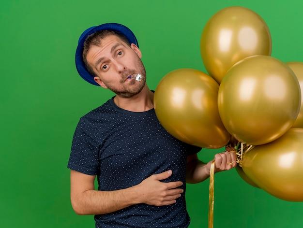 Разочарованный красивый кавказский мужчина в синей партийной шляпе держит гелиевые шары, дует в свисток, изолированные на зеленом фоне с копией пространства