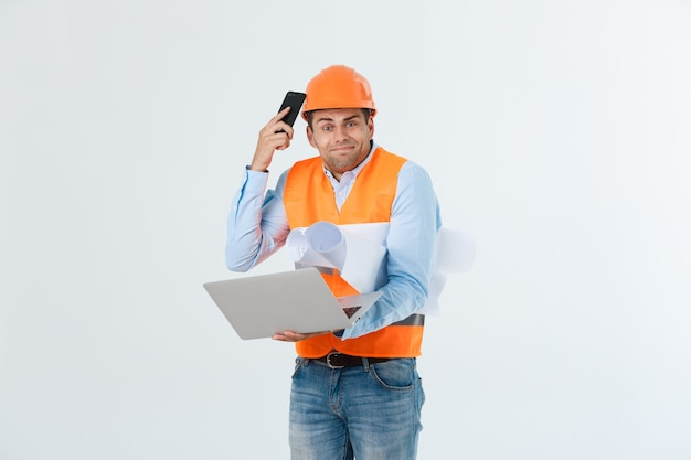オレンジ色のベストとヘルメットとジーンズを身に着けている、白い背景で隔離の失望したハンサムなエンジニア。