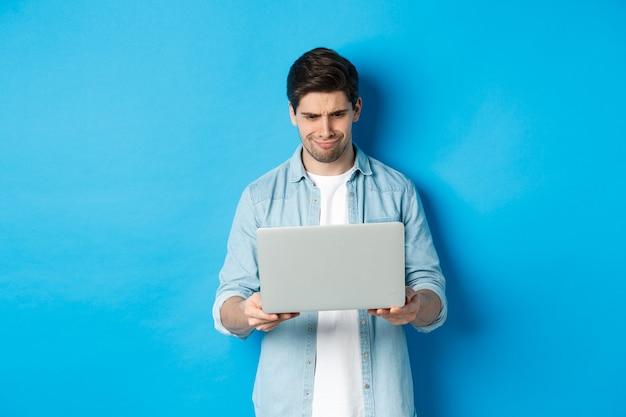 Разочарованный красавец смотрит на экран ноутбука и морщится, судя о чем-то плохом в интернете, стоит над синей стеной