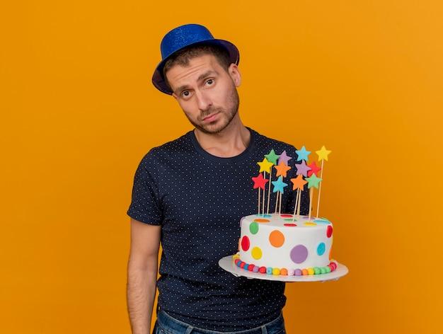 青いパーティー帽子をかぶって失望したハンサムな男は、オレンジ色の壁に分離されたバースデーケーキを保持