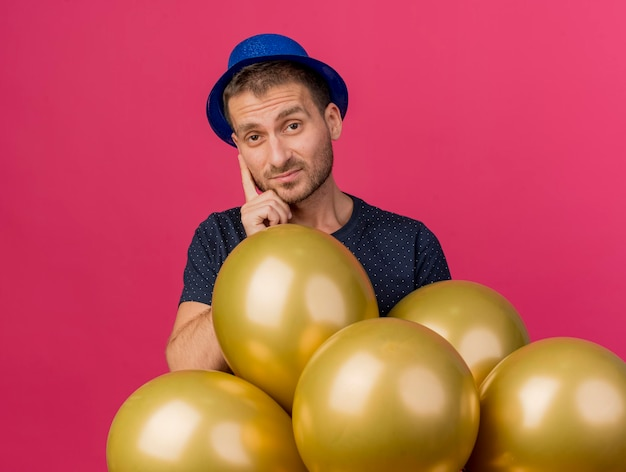 블루 파티 모자를 쓰고 실망 된 잘 생긴 남자는 복사 공간이 분홍색 벽에 고립 된 헬륨 풍선을 보유하고