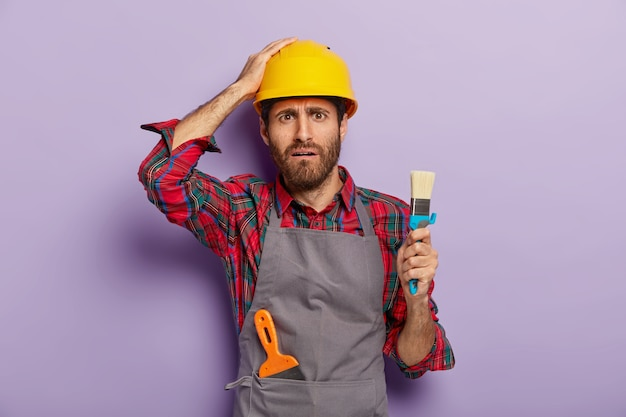 Disappointed industrial worker dressed in safety hardhat, casual uniform, holds brush for painting, being professional painter, has displeased face expression, isolated over purple wall