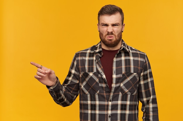 Disappointed irritated young man in checkered shirt with beard stading and pointing away to the side at copyspace over yellow wall