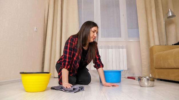 셔츠를 입은 실망한 여성은 밝은 현대 거실 바닥에 있는 컨테이너 근처에 깔개를 깔고 비가 온 후 천장에서 흐르는 물을 닦습니다.