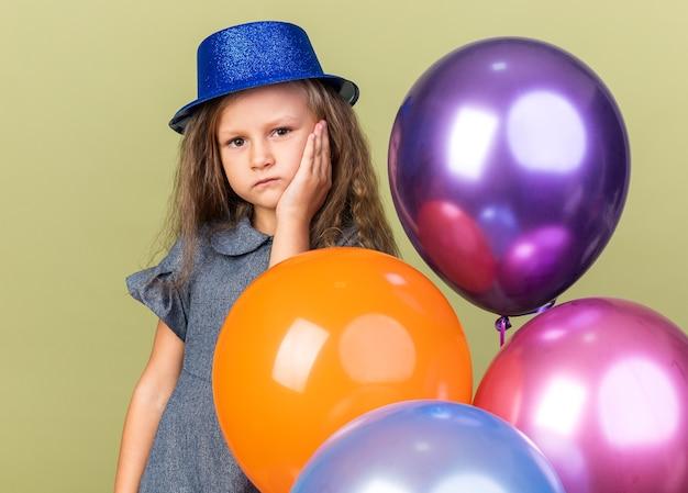 Bambina bionda delusa con cappello da festa blu che mette la mano sul viso e che tiene palloncini di elio isolati sulla parete verde oliva con lo spazio della copia