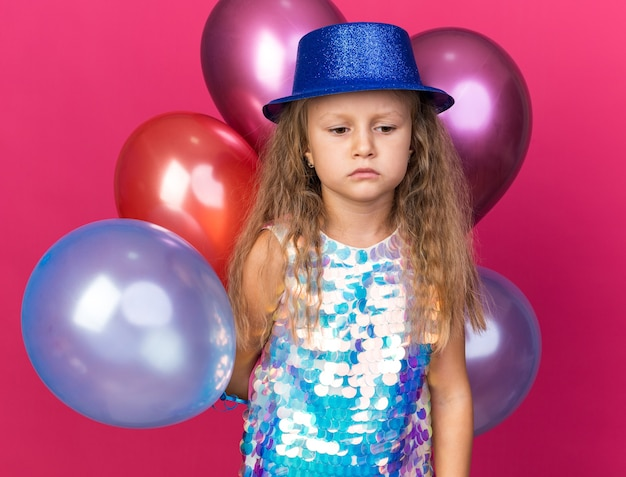 Disappointed little blonde girl with blue party hat standing with helium balloons isolated on pink wall with copy space