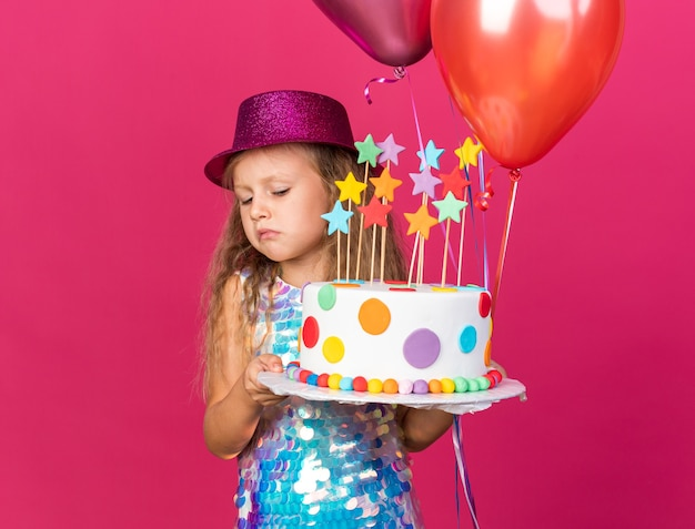 Disappointed little blonde girl with purple party hat holding helium balloons and looking at birthday cake isolated on pink wall with copy space