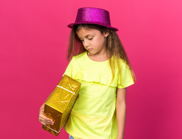 Disappointed little caucasian girl with purple party hat holding gift box isolated on pink wall with copy space