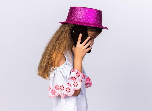 Delusa bambina caucasica con cappello da festa viola in piedi di lato parlando al telefono isolato sul muro bianco con spazio di copia