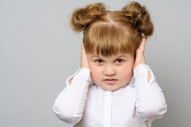 Disappointed little girl covering her ears