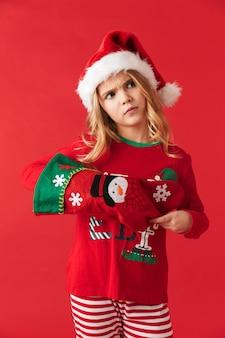 고립 된 크리스마스 의상을 입고 실망 어린 소녀, 크리스마스 양말에서 선물을 복용