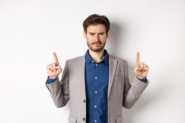 Разочарованный предприниматель мужского пола хмурится, указывая пальцами вверх и выглядит сомнительно, имея плохое предчувствие, стоя на белом фоне.