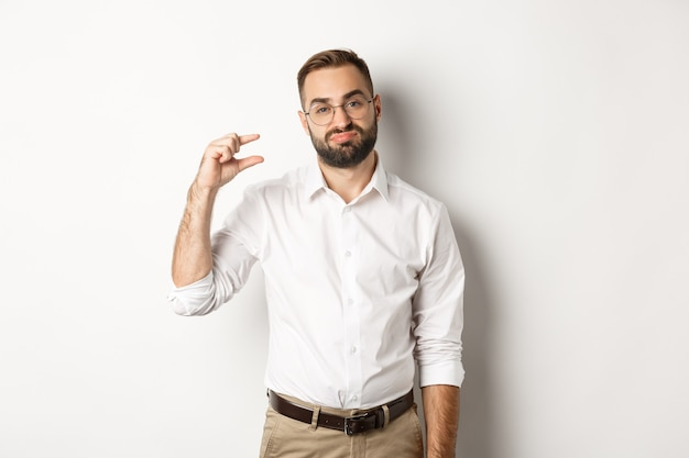 Disappointed male entrepreneur showing small object and sighing, standing over white background.