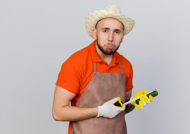 Разочарованный садовник-мужчина в садовой шляпе измеряет огурец рулеткой