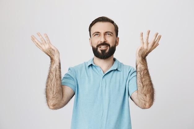 失望した男が不当な生活について不満を述べ、手を挙げて