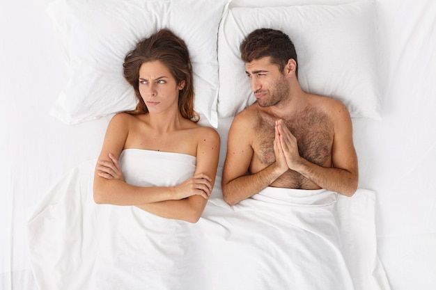 Disappointed man feels sorry, begs woman for forgiveness, have family conflict, unhappy woman turns aside with offended expression, doesnt want to talk with husband, pose in bedroom on white bed.