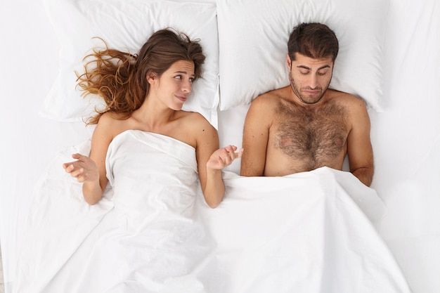 Disappointed man has erectile dysfunction during sex, his woman partner lies near under white blanket, puzzled with husbands impotence, spreads hands sideways. sexual problems. men health concept