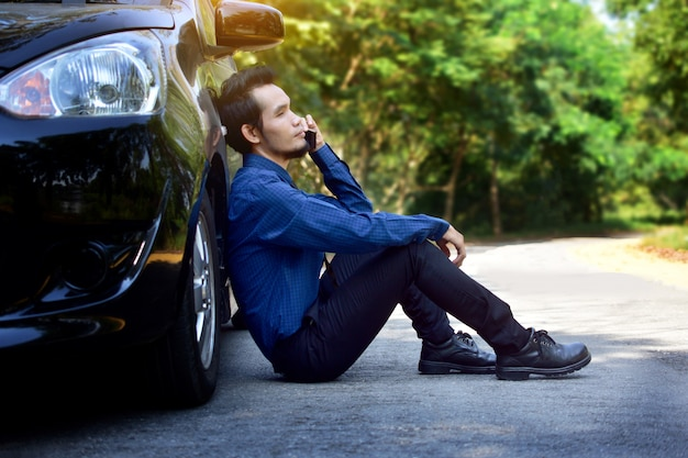 Disappointed man holding smart phone and sitting at car parked on road