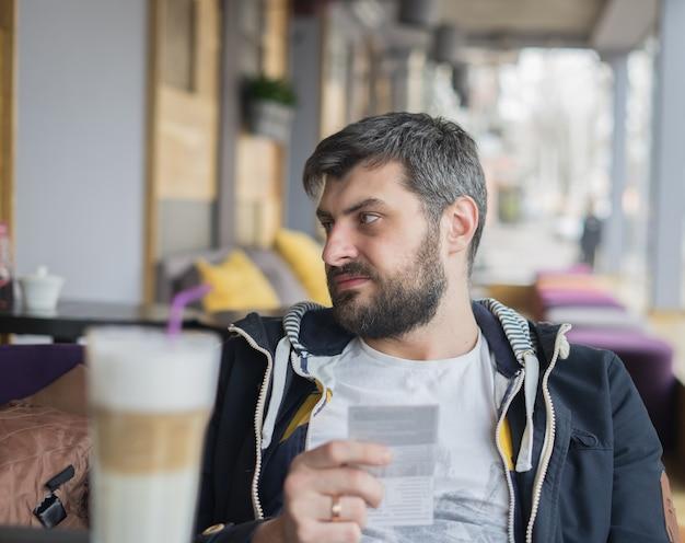Разочарованный мужчина получил большой счет в кафе или ресторане ему нужно заплатить слишком много денег