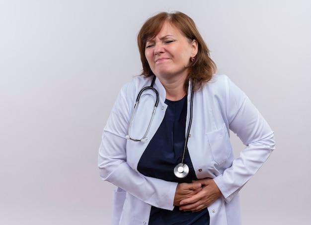 Medico donna di mezza età deluso che indossa veste medica e stetoscopio mani sui reni che soffrono di dolore ai reni sul muro bianco isolato con lo spazio della copia
