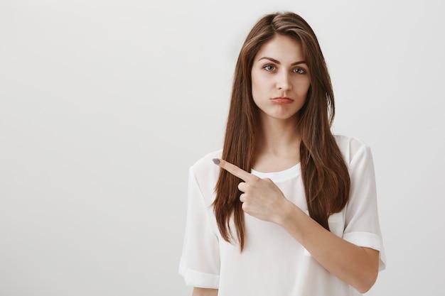 Разочарованная капризная девушка показывает пальцем влево и выглядит расстроенной