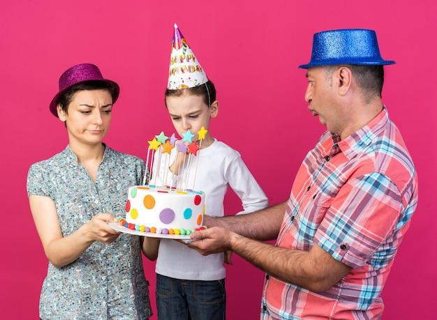Madre e padre delusi con cappelli da festa che tengono insieme la torta di compleanno guardando il loro figlio scontento isolato sul muro rosa con spazio copia