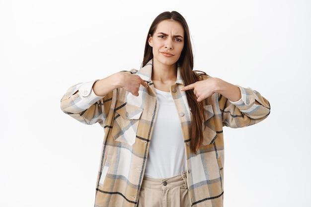 Разочарованная или сомневающаяся молодая женщина указывает на себя, хмурится и выглядит неохотно, скептически относится к победе, недовольно стоит у белой стены
