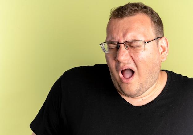 明るい壁の上に立っている大きく開いた口を持つ黒いtシャツを着て眼鏡をかけている失望した太りすぎの男