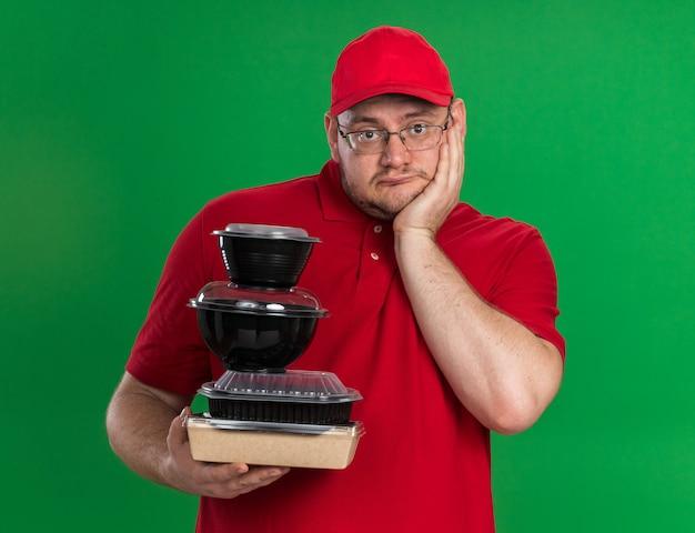 Deluso sovrappeso giovane fattorino in occhiali ottici tenendo contenitori per alimenti e mettendo la mano sul viso isolato sulla parete verde con spazio copia
