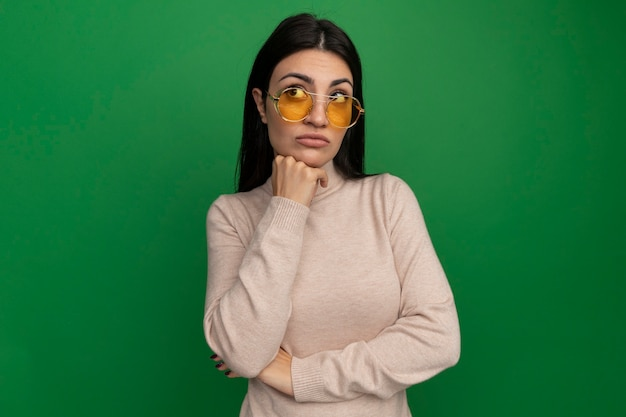 태양 안경에 실망 된 예쁜 갈색 머리 백인 여자는 턱에 손을 넣고 녹색 측면에서 보인다