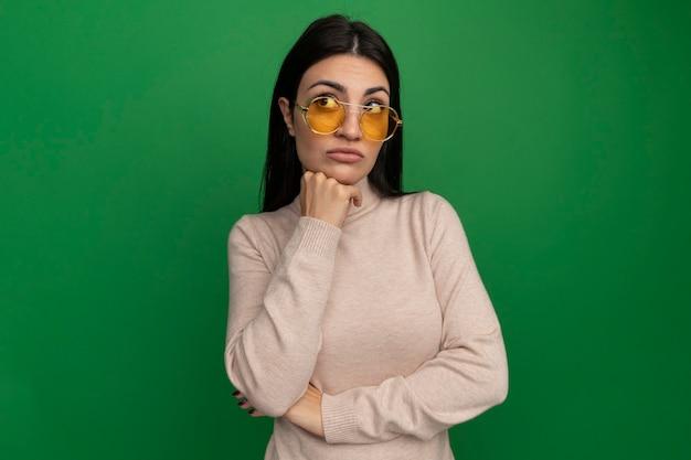 La ragazza caucasica deludente abbastanza mora in occhiali da sole mette la mano sul mento e guarda a lato sul verde