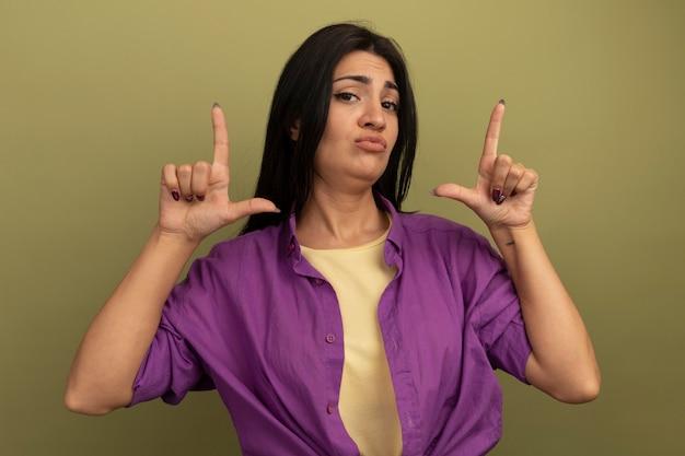 La donna graziosa deluso del brunette indica con due mani isolate sulla parete verde oliva