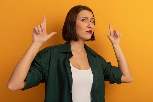 오렌지 벽에 고립 된 두 손으로 실망 예쁜 여자 포인트