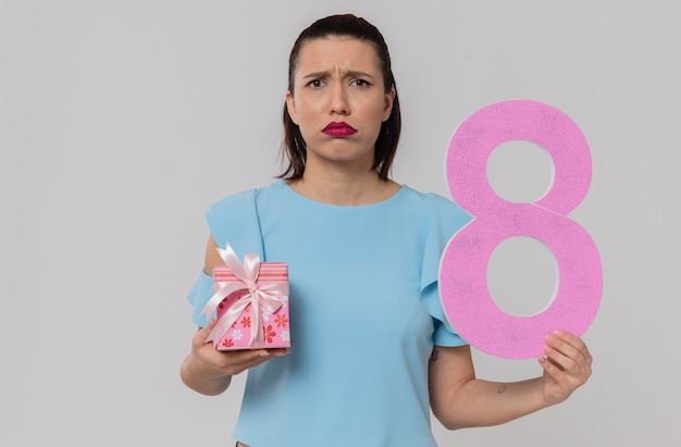 Disappointed pretty young woman holding pink number eight and gift box