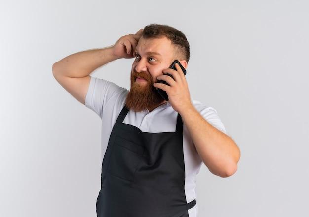白い壁の上に立っている混乱した引っかき頭を脇に見て携帯電話で話しているエプロンで失望したプロのひげを生やした床屋の男