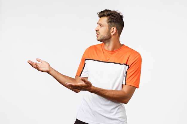 Disappointed sad bearded masculine male trainer in sports t-shirt