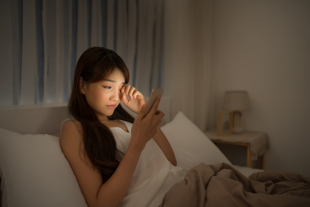 Disappointed sad woman holding mobile phone while lying on bed at night