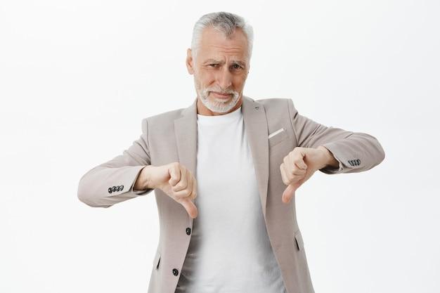Разочарованный старший бизнесмен показывает палец вниз и недовольно хмурится