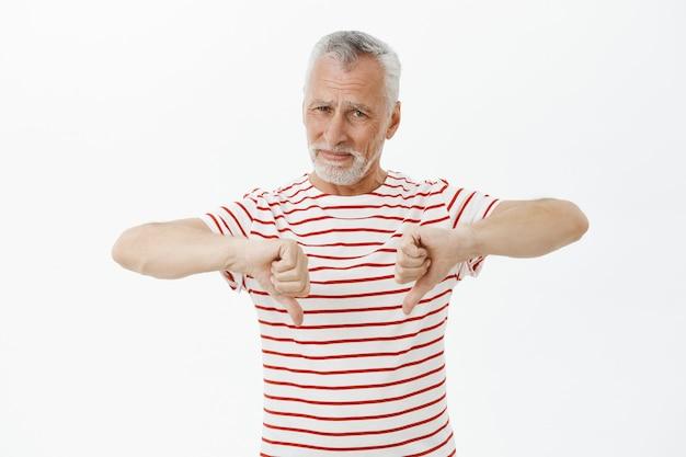 Разочарованный старший мужчина в футболке показывает палец вниз, показывает жест неприязни