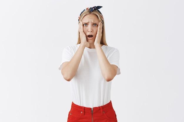 Разочарованная шокированная молодая девушка выглядит расстроенной и обеспокоенной