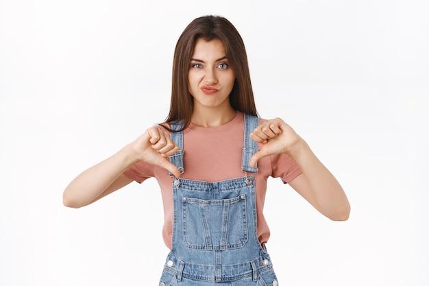 Разочарованная скептически высокомерная привлекательная женщина в комбинезоне, футболке, неудовлетворенная ухмылка, показывающая палец вниз и хмурящаяся в знак несогласия, выражает неприязнь, судит что-то ужасное