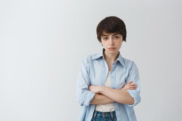 La giovane ragazza maschiaccio delusa e scettica incrocia il petto con le braccia e sembra giudicante