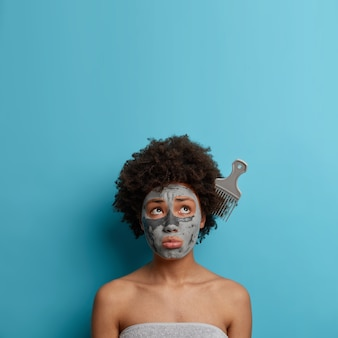 Disappointed stressful woman has problematic curly hair, stuck comb, expresses displeasure, applies clay mask, cares about body and complexion, wrapped in towel, isolated on blue wall, copy space