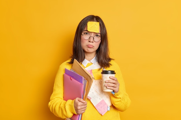 Disappointed tired female graduate prepares for examination session has deadline surrounded by sticky notes and papers holds disposable cup of coffee has unhappy displeased expression stands indoor