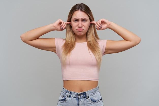 失望した不幸な金髪の若い女性は指で耳を閉じ、灰色の壁に失望しているように見える