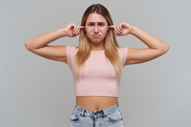 Disappointed unhappy blonde young woman closed ears by fingers and looks disappointed over gray wall