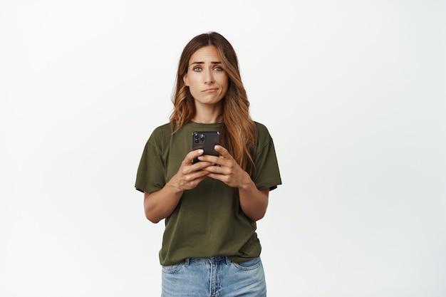 Donna di mezza età delusa e sconvolta che tiene in mano smartphone, sopracciglia solcate e sorrisetto con faccia triste