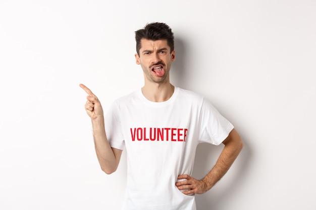 Разочарованный волонтер показывает плохое промо-предложение, высунув язык и с отвращением гримасничает, показывает пальцем влево, одет в белую футболку организации.